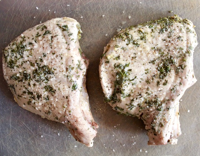 two pork chops with herbs on cutting board