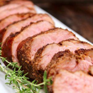 sous vide pork tenderloin with coffee rub on white platter