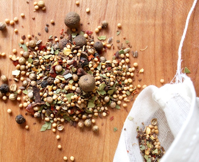 tiny pile of pickling spices on wood counter