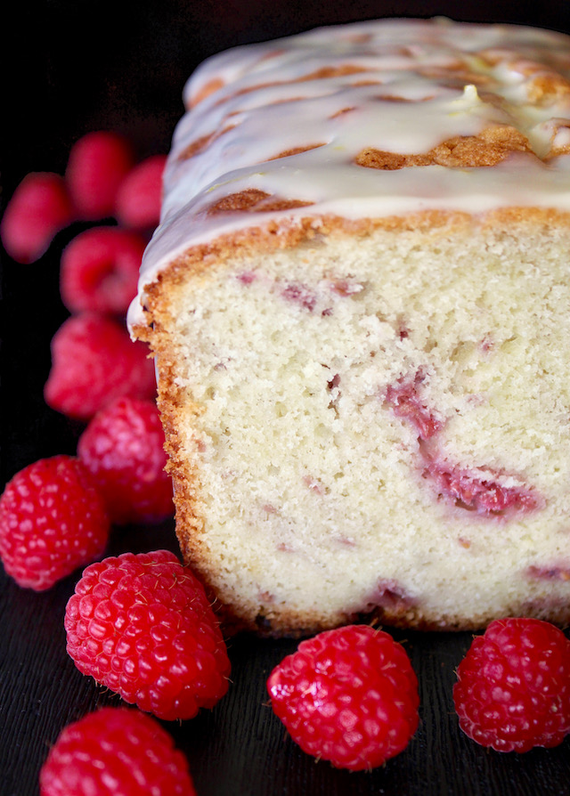 Cross section of White Chocolate and Raspberry Loaf Cake surrounded by fresh raspberries