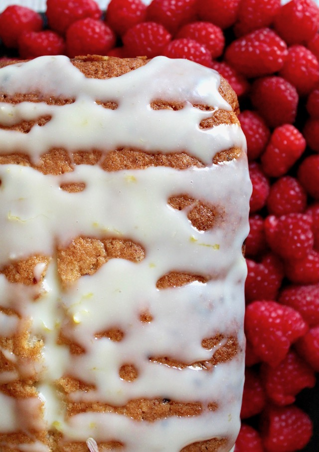 top view of White Chocolate and Raspberry Loaf Cake surrounded by fresh berries