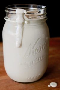 Cashew cream spilling over mason jar rim