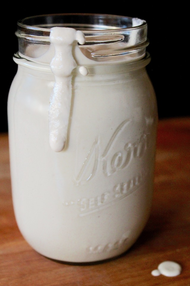 Cashew cream spilling over mason jar rim