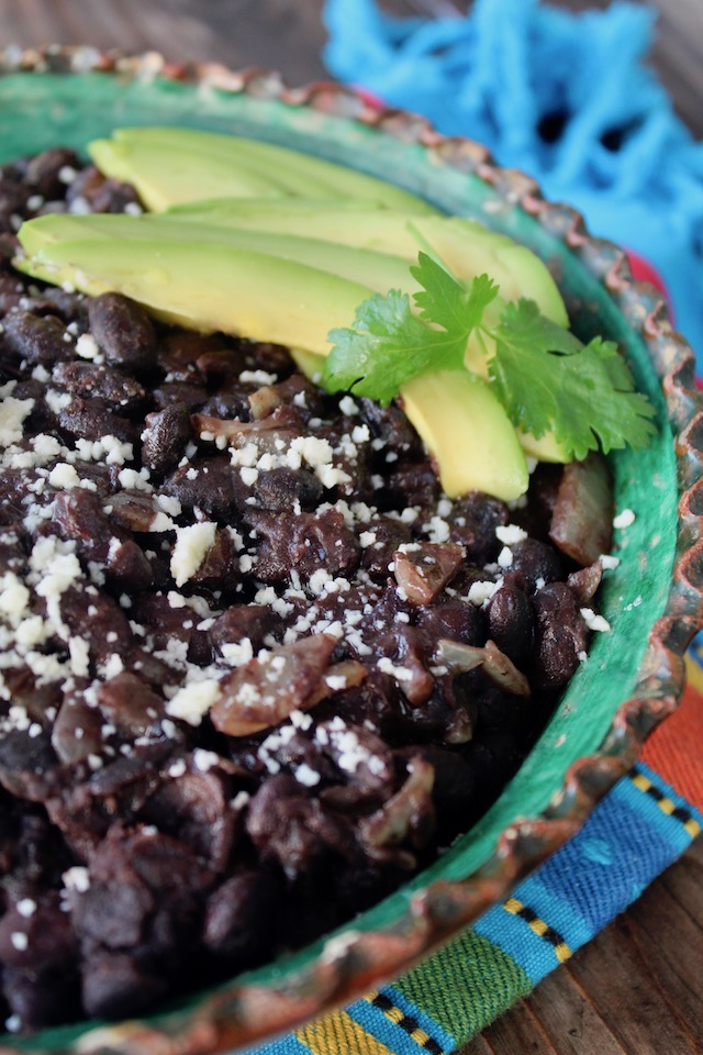 close up of black beans with avocado slices and cilantro in green rimmed bowl