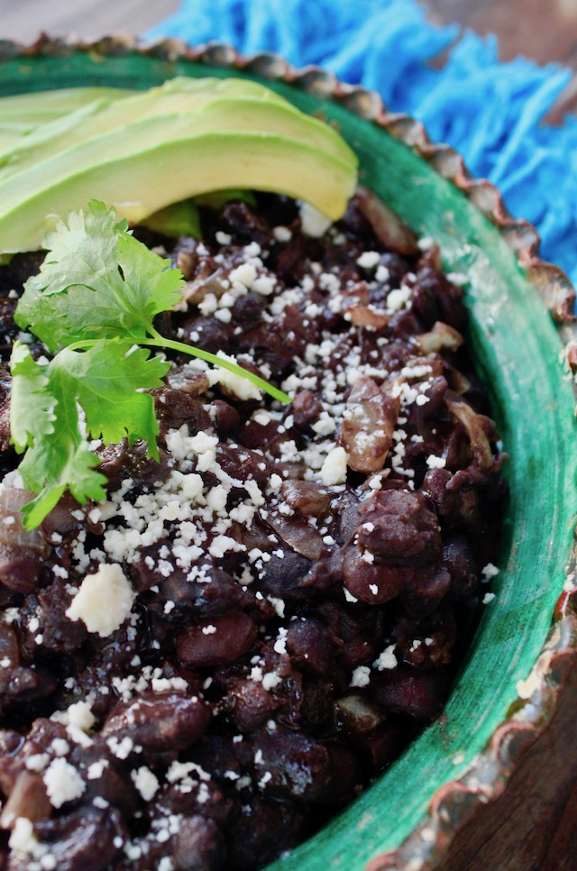 black beans with avocado slices and cilantro in green rimmed bowl