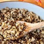cooked wild rice in an orange pot with a wooden spoon