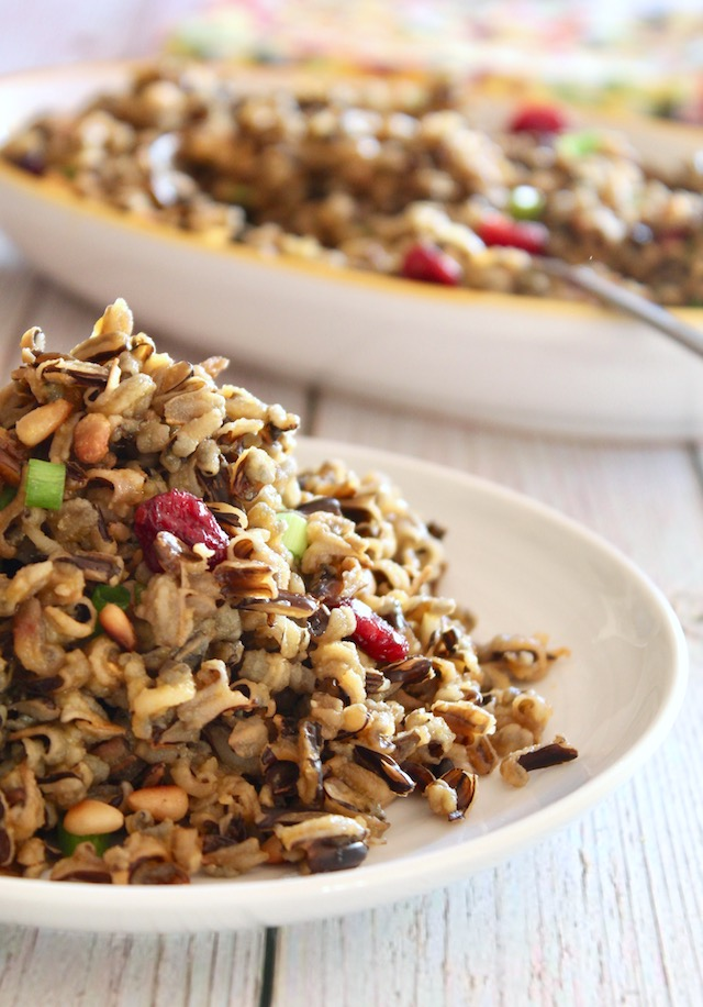 close up of cranberry wild rice on a white plate in front of platter