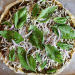 whole, raw pizza with basil leaves on top