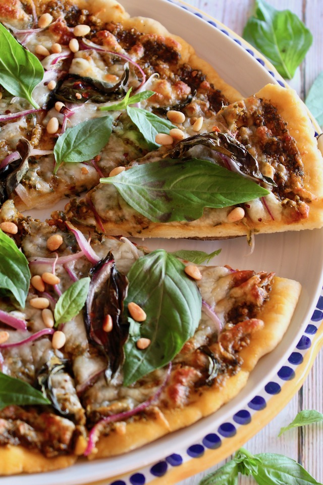 Basil Pizza with one slice being taken