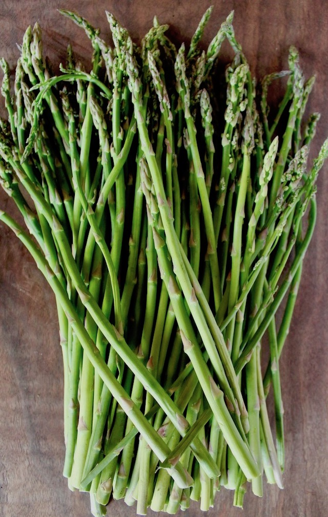 pile of skinny asparagus on cutting board