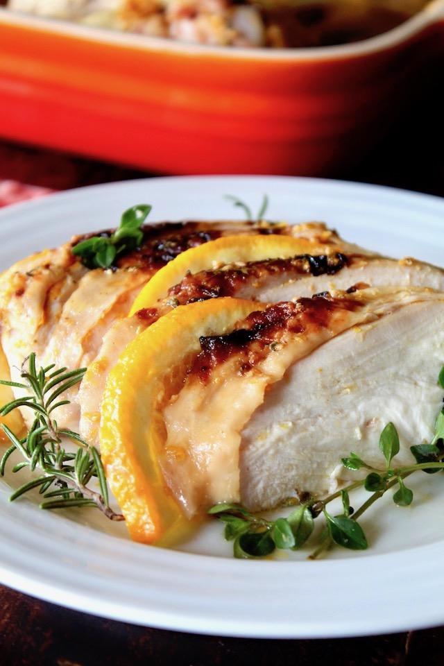 Sliced chicken with golden skin and orange slices
