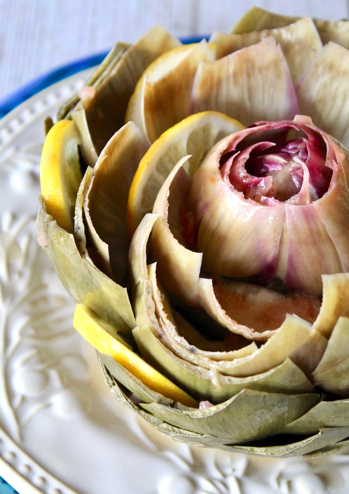 Steamed artichoke with lemons slices between the leaves on a white plate