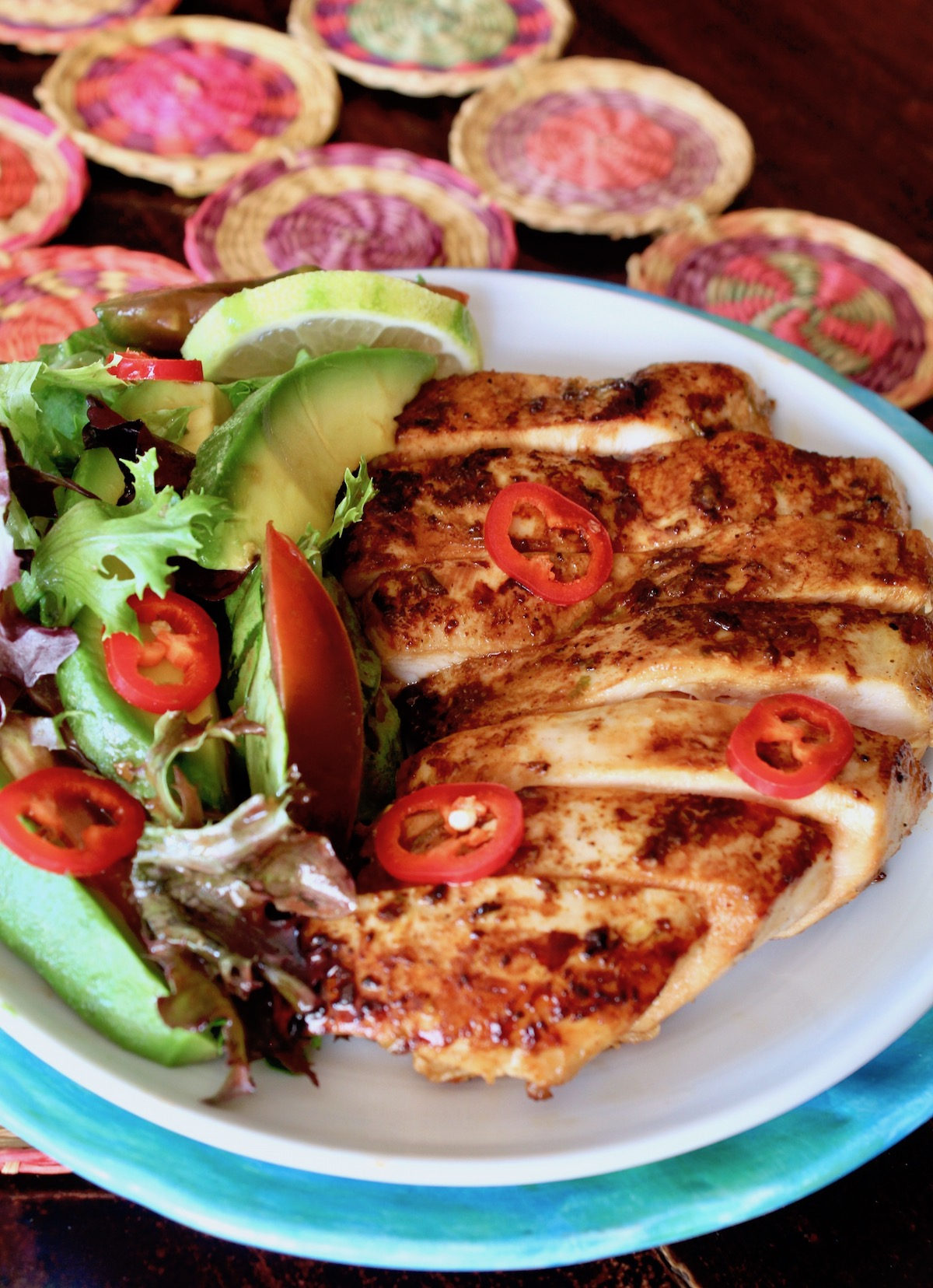 sliced tequila lime chicken on white plate with a side salad